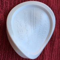 Weck canning jar lid in plastic, somewhat warped from falling to lower dishwasher rack