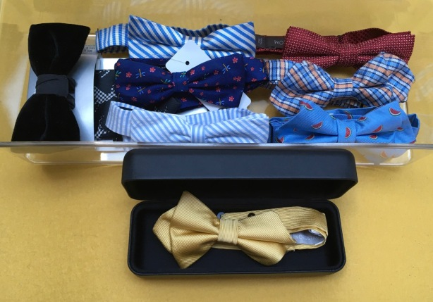 7 colorful bow ties in acrylic storage case next to yellow tie in a protective eyeglass case
