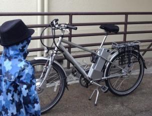 child standing next to silver e-bike
