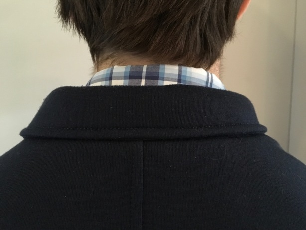 plaid collar of shirt visible above jacket neckline