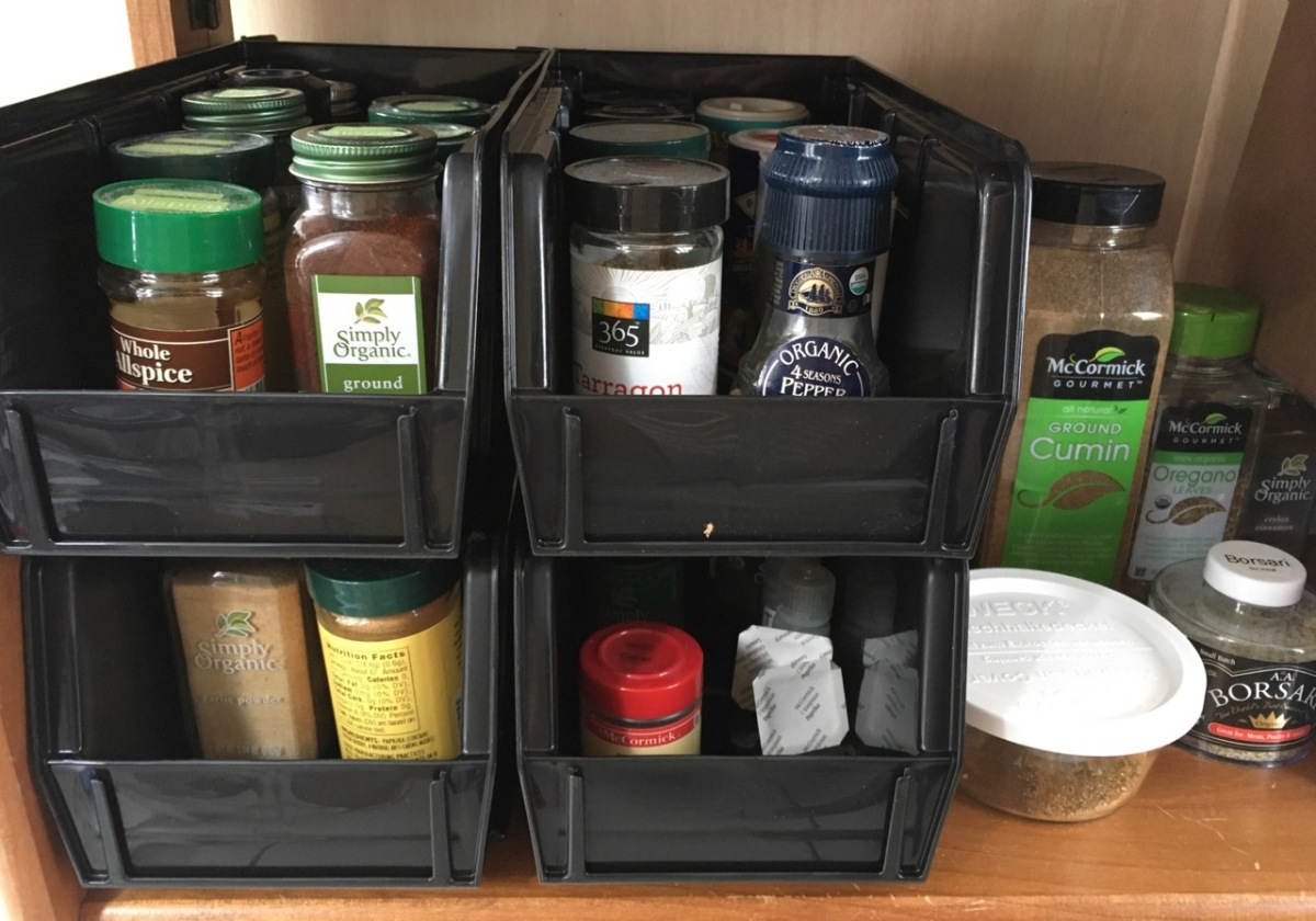 Wooden shelf with 4 AkroBins holding assorted spice jars with larger containers alongside