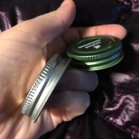 Green Simply Organic lid next to silver toned Whole Pantry lid