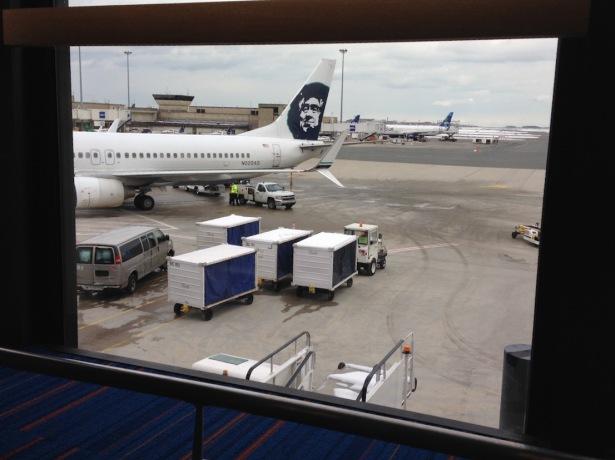 Tail of Alaska plane visible on tarmac through airport terminal window